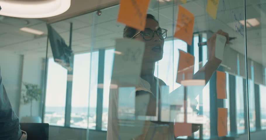Business woman presenting her ideas to male colleague on sticky notes over glass wall. Business man and woman brainstorming in modern office.  | Shutterstock HD Video #24537179