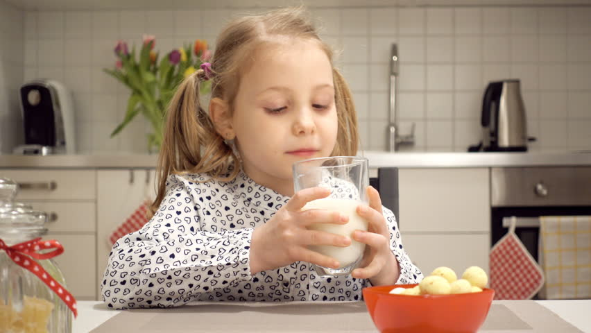 Happy pretty child girl drinking milk and having fun in white kitchen at home