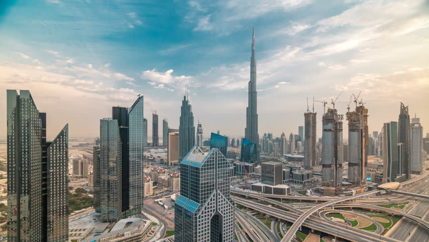 Dubai downtown skyline timelapse at sunset with beautiful city center skyscrapers and Sheikh Zayed road traffic. Top aerial view from tower rooftop. Clouds on the sky. Dubai, United Arab Emirates