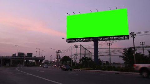 Advertising billboard on sidelines of road with day to night time lapse