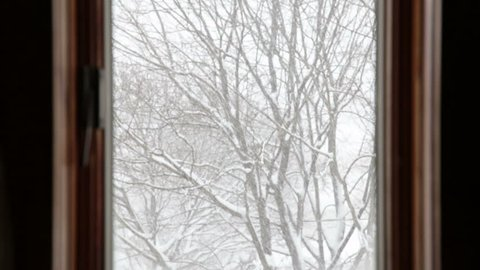 Looking out of a window to heavy falling snow outside on trees upstate New York winter
