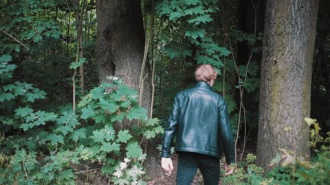 Scary maniac caucasian man in black leather jacket pulls out knife stucked in tree, stare into camera and walk into woods with cat