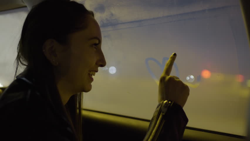 """Happy Mixed Race Teen Draws A Peace Sign, Hearts, Stars, And Writes The Word """"Love"""" On Foggy Window In Backseat Of Moving Car"""