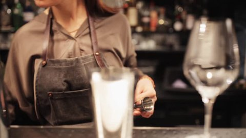 alcohol drinks, people and luxury concept - barmaid with shaker and jigger preparing cocktail at bar