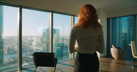 Young business woman is part of a modern office skyscraper in talks on the phone, steadicam shot
