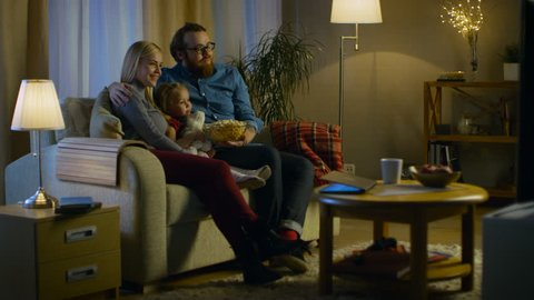 Long Shot of a Father, Mother and Little Girl Watching TV. They Sit on a Sofa in Their Cozy Living Room and Eat Popcorn. It's Evening. Shot on RED EPIC-W 8K Helium Cinema Camera.