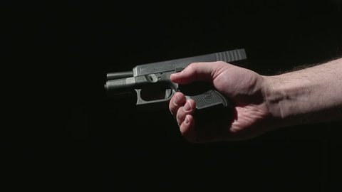 Hands Loading a Gun Clip and Unloading Clip and Round. side profile of someone holding a gun and loading a clip. Loads chamber, unloads clip and ejects shell from barrel