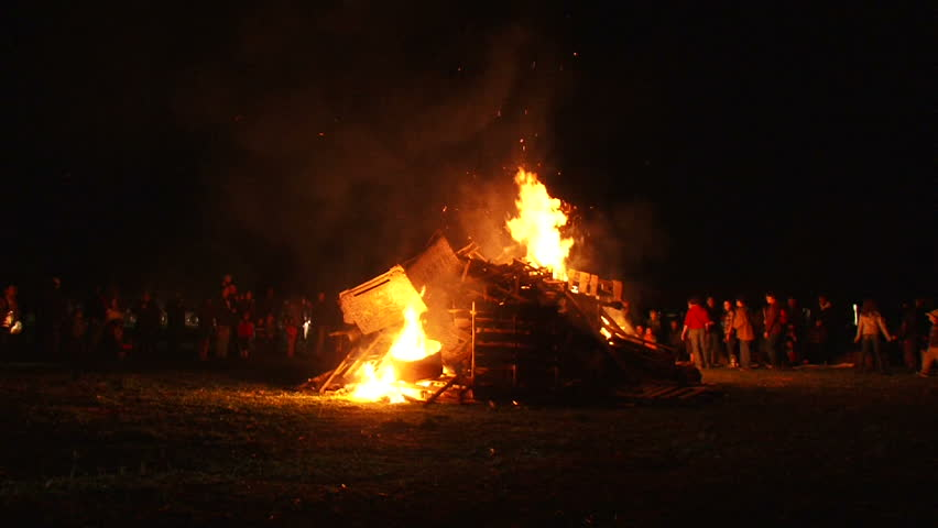 Unrecognizable people watch as huge bonfire gets lit and burns at night, time lapse.