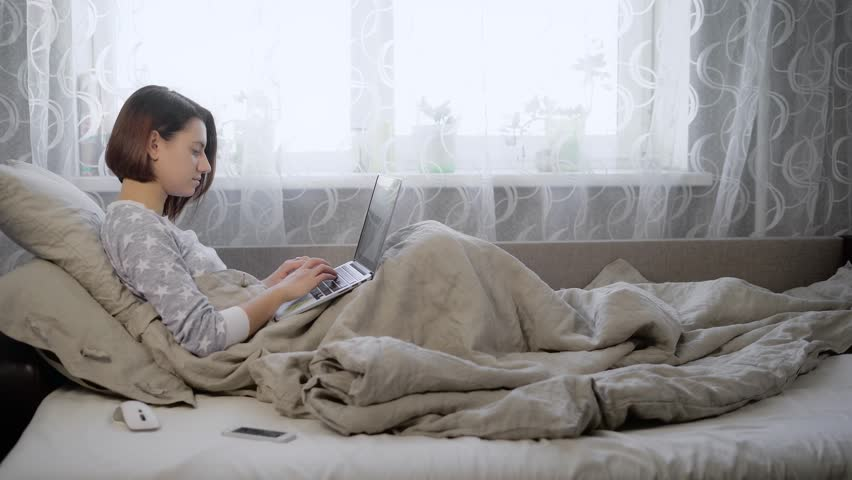 young girl with brown hair dressed in a gray sweater sitting in bed