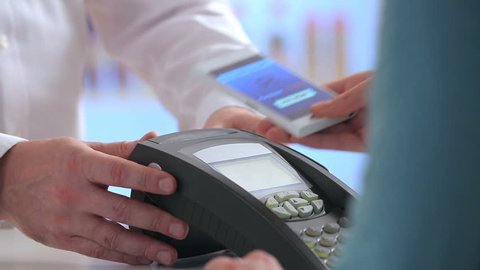 Woman paying through smart phone using NFC technology. Close up.