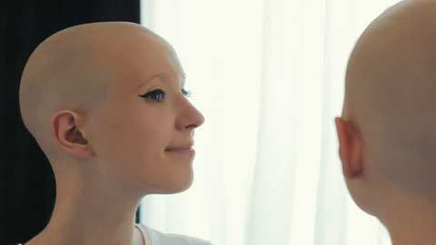 Happy cancer woman survivor looking at herself in the mirror
