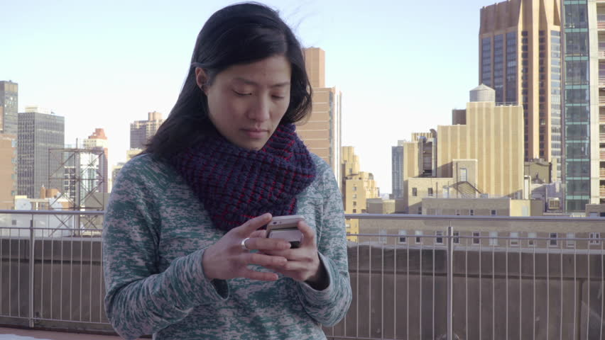 Beautiful young Vietnamese hipster girl living in New York City uses her smart mobile cell phone to text message friends standing on rooftop with Manhattan sykline in background