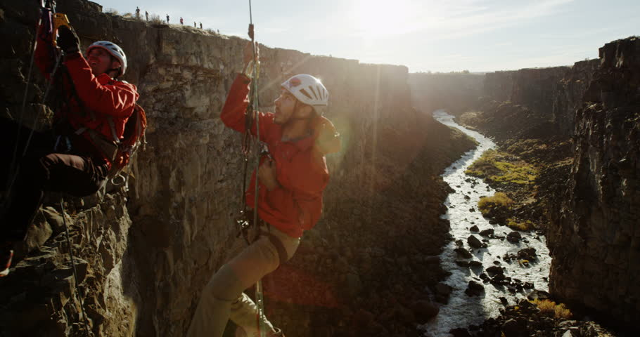 Steadicam past two rock climbers going up ropes in a deep canyon during sunset