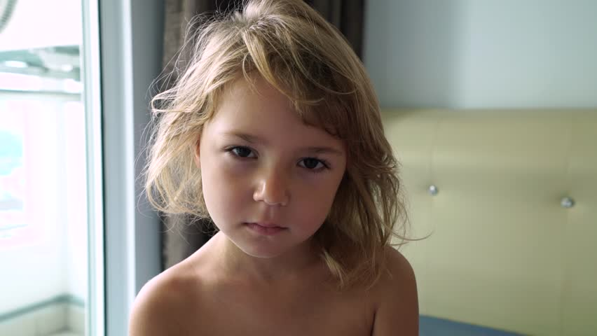Close-up of awakened cute girl sitting in her bed with a sullen expression on face