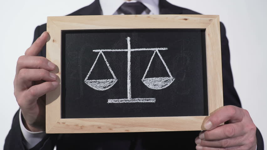 Justice scales drawn on blackboard in lawyer hands, decision pros and cons