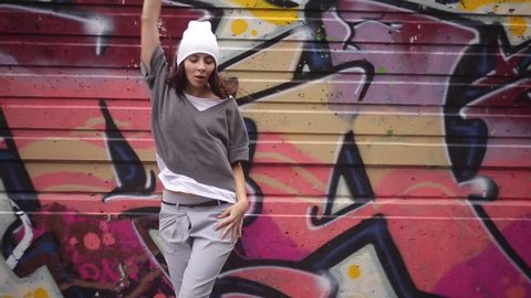 The girl is dancing against the graffiti background.