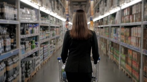 Woman shopping at the supermarket, follow shot from back of young woman with trolley in shopping center, alcohol store.