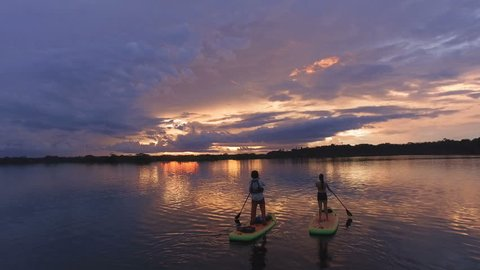 Aerial - A group doing SUP yoga on paddleboards in a star shape with sky reflection - Amazon, Ecuador
