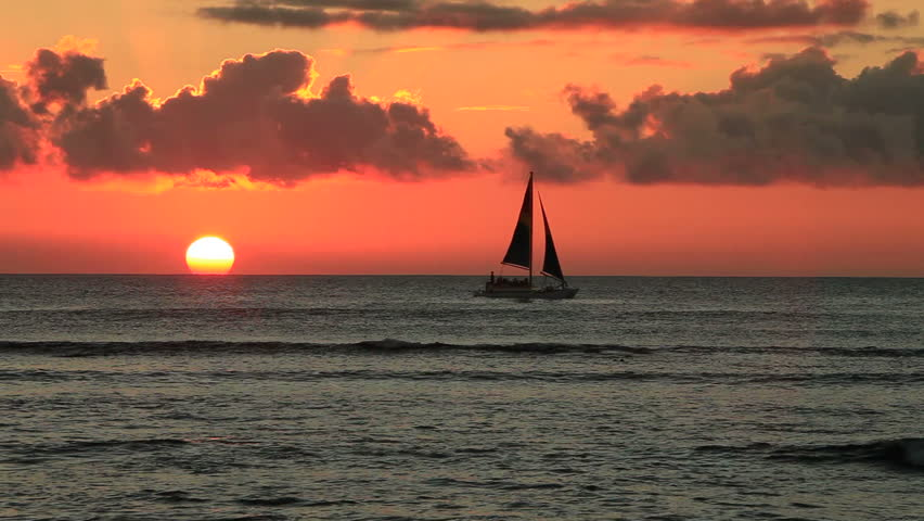 A sailboat crosses the horizon during a sunset off the shore of Hawaii.