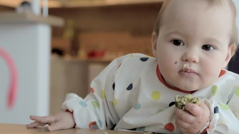 Eleven months old baby feeding herself with her fingers, baby led weaning; concept of motherhood and parenting