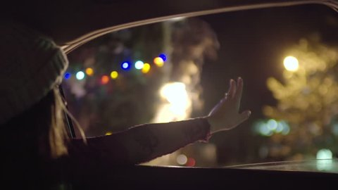 Excited Young Woman Holds Her Hand Out Moving Car Window At Night In Beautifully Lit Winter Wonderland
