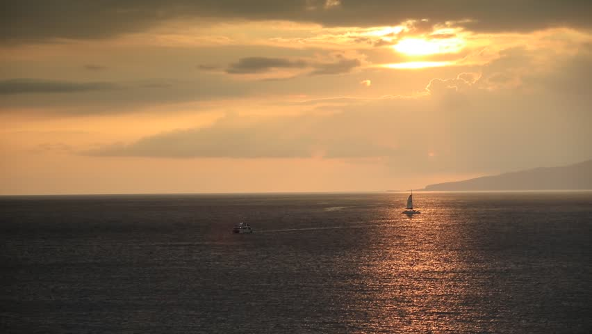 Ocean sunset lit with golden light over the sky and shinig water with a sailboat under sun disc | Shutterstock HD Video #24886919