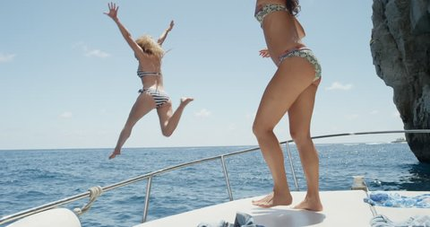 Women jumping off boat into ocean two girls jump into clear blue water from sailboat enjoying active lifestyle summer holiday travel vacation adventure