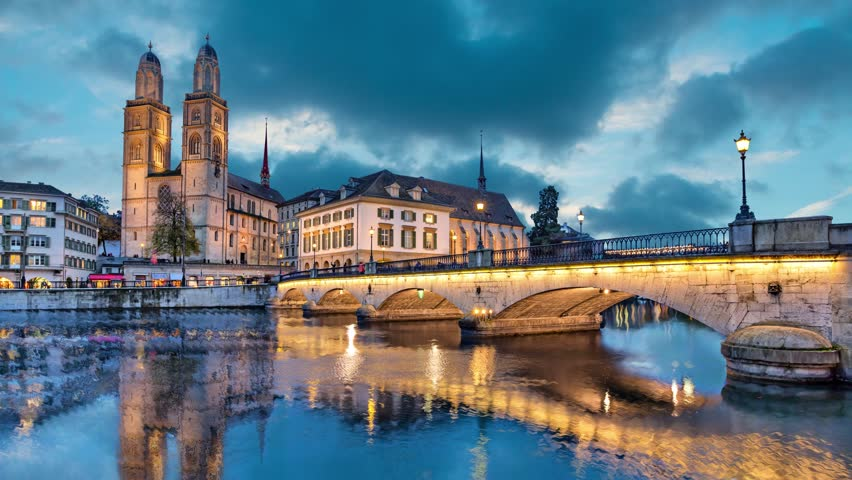 Munsterbrucke and Grossmunster church reflecting in river Limmat, Zurich, Switzerland (static image with animated sky)