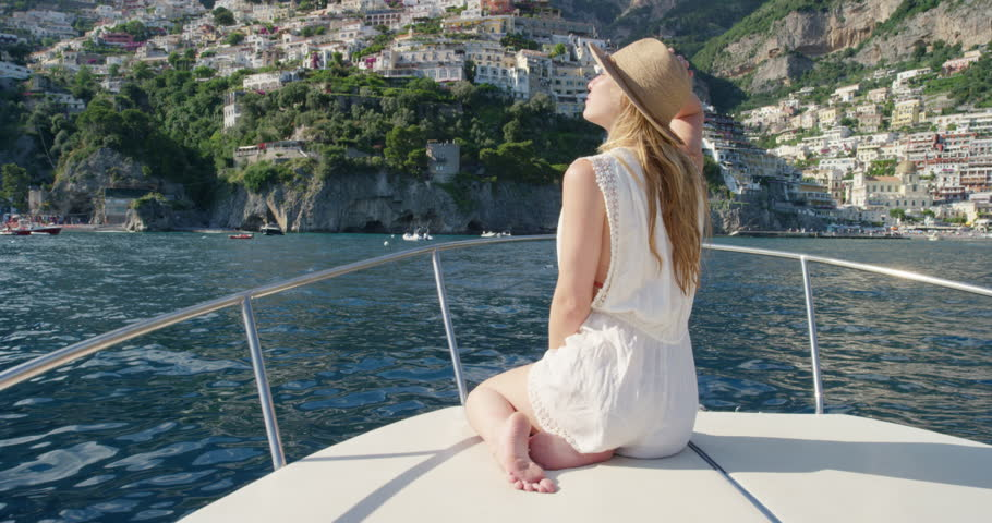 Tourist woman looking at view of Italian coastal Town from boat wearing summer playsuit and straw hat enjoying European summer holiday travel vacation adventure in Positano Amalfi Coast Italy