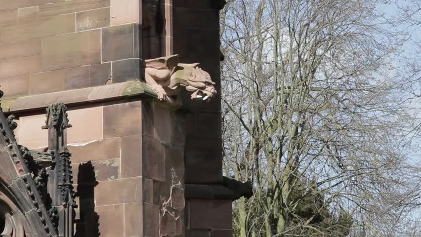 An Ugly Gothic Gargoyle Dragon looms from the stone walls of Lichfield Cathedral, hand carved and impressive, an architectural treat for the eyes.