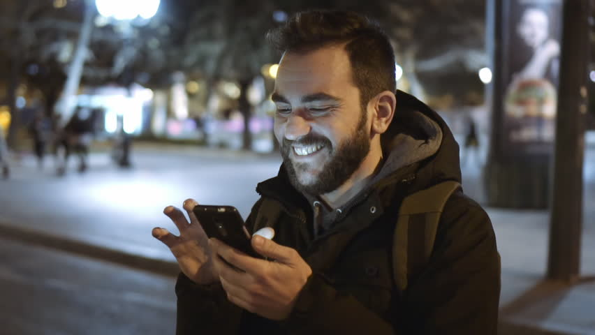 A smiling cheerful young man is commuting to work while browsing his cellphone on a busy urban street at night. 100fps slowmotion.