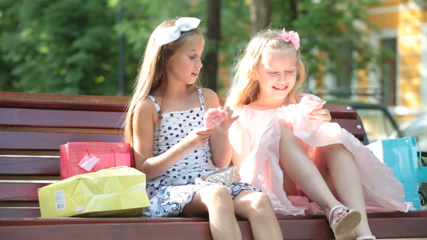 fashionable little girls conversation on a bench in the