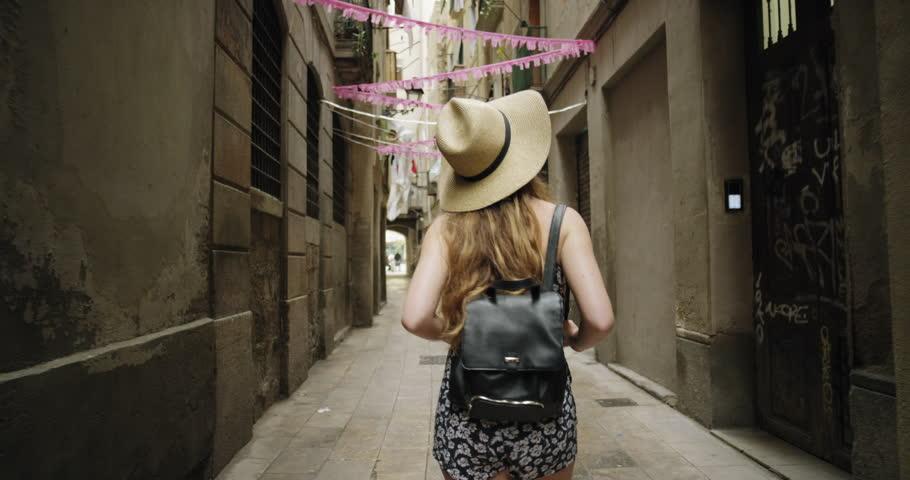 Tourist woman exploring walking narrow streets of Barcelona Wearing cute summer dress enjoying European summer holiday travel vacation adventure Rear view #24944519