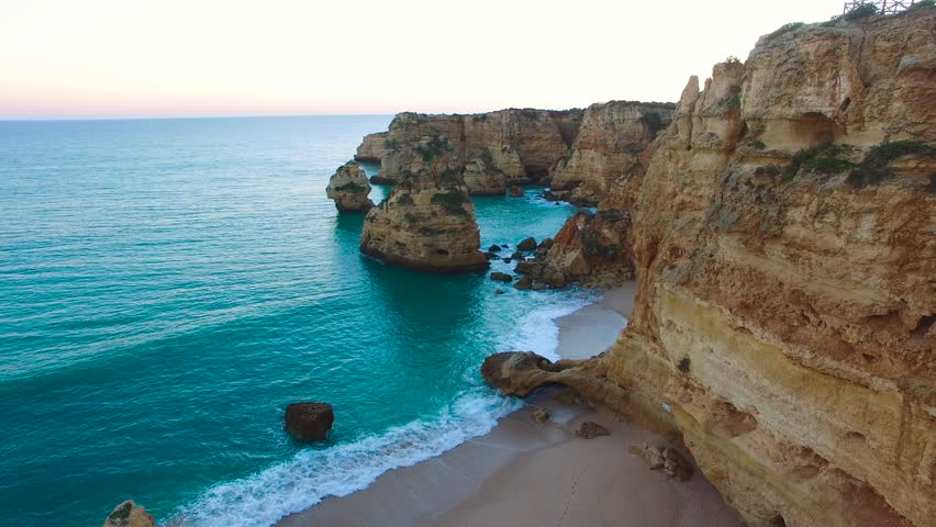 4K Drone Aerial beautiful rock formations of Marinha Beach, Praia da Marinha, Algarve Portugal, seagull flies through the scene, teal colored water