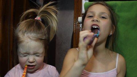 Two little sisters brush their teeth