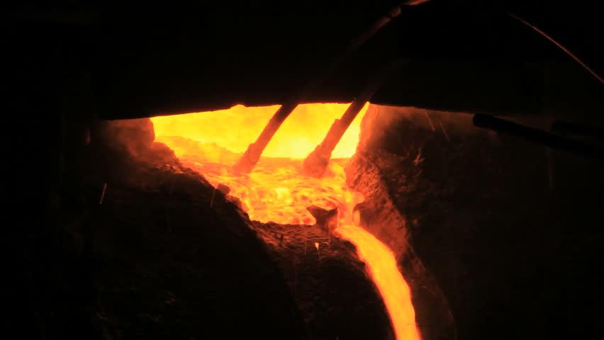 Molten metal start pouring from blast furnace. Metallurgical industry. Liquid metal in metal furnace. Liquid metal production process