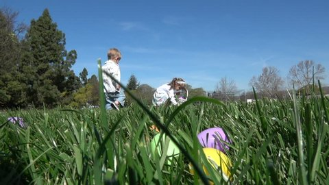 Slow motion of kids having fun gathering eggs at Easter hunt