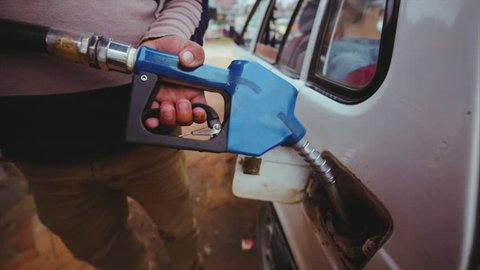 Close view of man's hands holding petrol pump. Refuelling car at petrol station. Driver locks the tank tap with key. Kathmandu, Nepal
