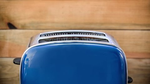 Seamless loop - Toast popping out of vintage blue toaster, wooden background, HD video