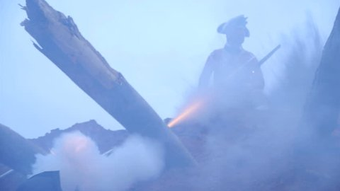VIRGINIA - OCTOBER 2014 - Reenactment, large-scale, epic American Revolutionary War anniversary recreation -- in the middle of battle.  Explosions rock trenches, Brit Soldier killed by Patriot Musket