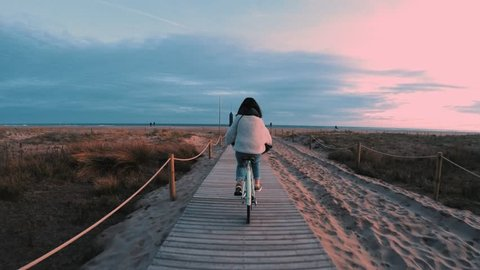 Wide shot from behind, camera follows girl on mint bicycle cycling at sunset time to sand beach next to sea shore, she stops at the end and dreamily looks forward while smile
