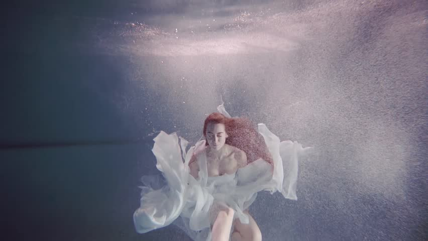 young woman with long red hair swimming underwater like a fairy tale
