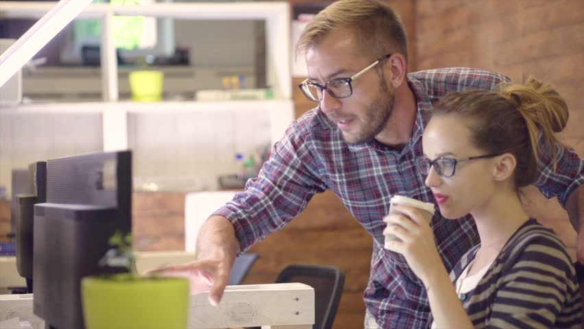 Young Casual business couple using computer in the office. Two colleagues working together on an innovative product design in creative studio. Coworking, manager showing new startup idea. Slowmo 4K