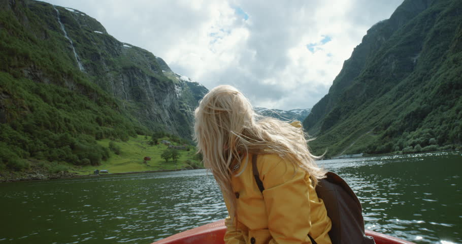 Woman sitting in boat on Fjord Norway hair blowing in wind traveling towards scenic landscape nature background view enjoying vacation travel adventure | Shutterstock HD Video #25058648