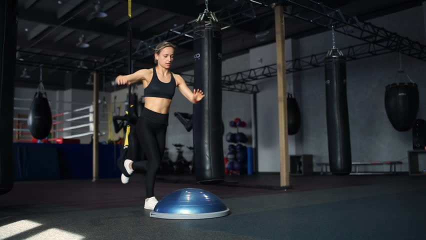 Fit woman in black sportswear doing lunges on the Bosu and the TRX in gym