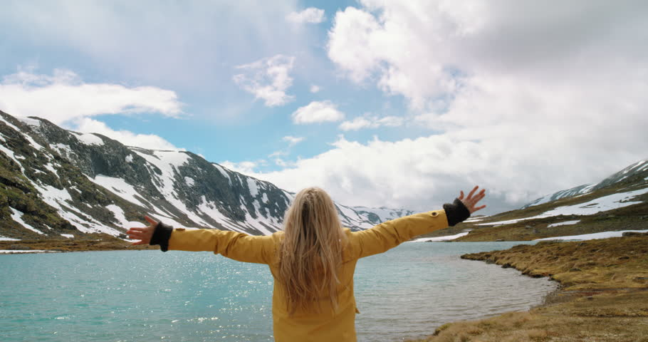 Woman with arms raised by lake looking at snowy mountain view lifting arm up celebrating scenic landscape Girl wearing yellow jacket enjoying vacation travel adventure nature Norway