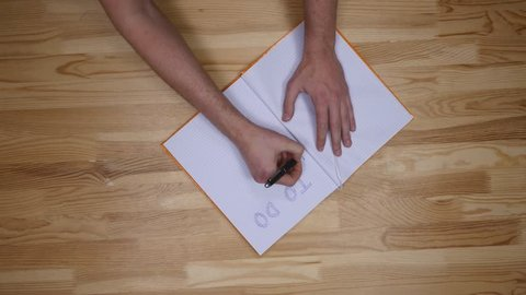 man hand writing to do list on notepad, top view.