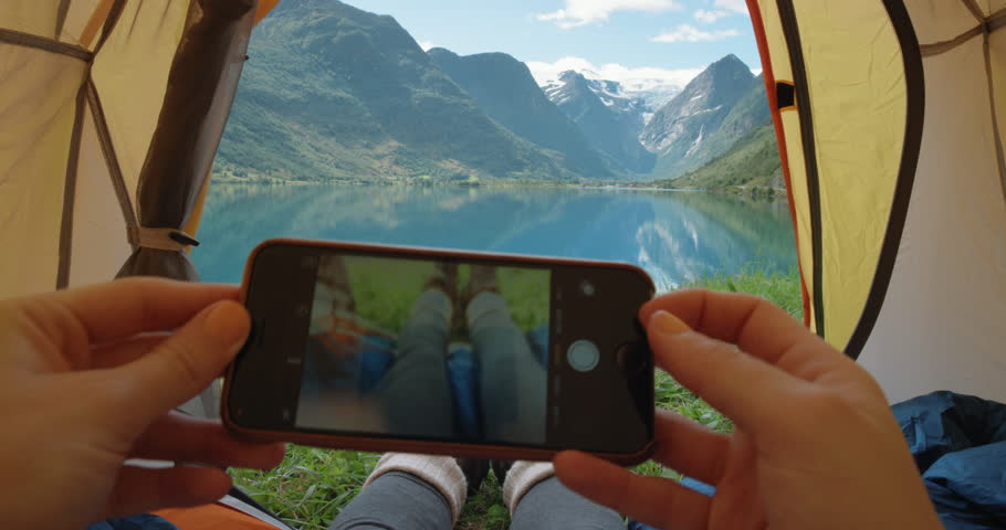 Camping woman lying in tent taking photo of feet with smart phone Close up of Girl wearing hiking boots relaxing on vacation POV Norway #25065449