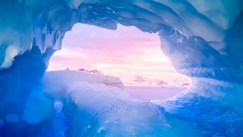 Blue ice cave in Antarctica covered with snow and flooded with soft sunset pink light. Exploring beauty world. Travel background. Slow motion 4K footage