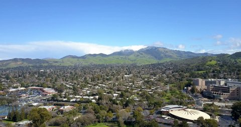 Flying over areal view of Walnut Creek with peaks of Mount Diablo covered with spring snow at background